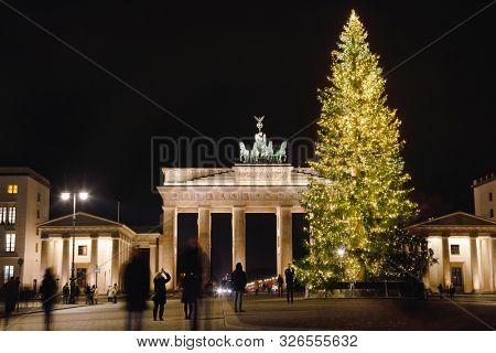 Berlin, Germany - December 12, 2018: Illuminated Neoclassical Brandenburg Gate (Brandenburger Tor) and Christmas Tree as viewed from the Pariser Platz