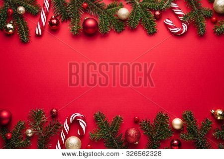 Merry Christmas and happy New Year border frame on red background. Festive decor of fir branches, Christmas balls and candy cane
