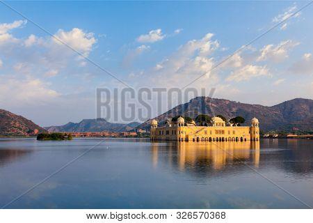 Rajasthan landmark - Jal Mahal (Water Palace) on Man Sagar Lake on sunset with dramatic sky. Jaipur, Rajasthan, India