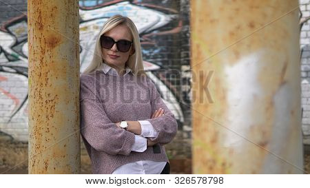 Showy Woman In Sweater Posing Among Rusty Metal Pillars .