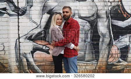 Husband And Wife Hugging On Grafitty Backgroundcouple And Relationship. Concept Of Seasoned Love