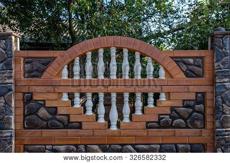Brown Decorative Stone Fence With Baluster. Against The Green.