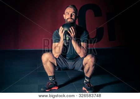Young Bearded Atletic Man Holding Kettlebell And Doing Squats In The Modern Gym. Man During Workout