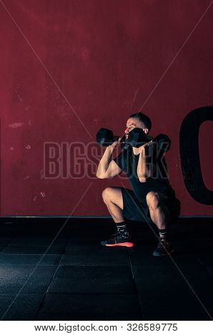 Young Bearded Atletic Man Holding Dumbbell  And Doing Squats In The Modern Gym. Man During Workout G