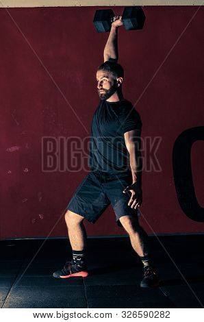 Young Bearded Athletic Man Is Training With Heavy Dumbbell In A Modern Gym. Workout With Dumbbell. A
