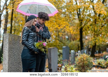 Couple in grief on a cemetery in fall while it is raining