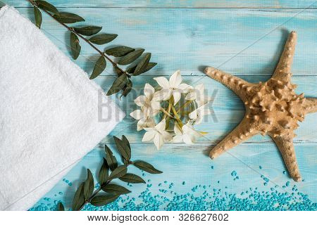 Spa And Wellness Setting With Flowers, And White Towel On Old Wooden Background. Blue Dayspa Nature