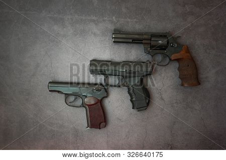 Firearms Laid Out Along The Line. Three Guns Close-up On A Gray Concrete Background. Copy Space.