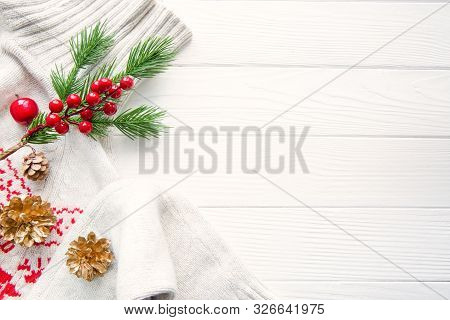 White Woolen Sweater With Christmas Ornament On White Wooden Background. Christmas Red Decoration. S