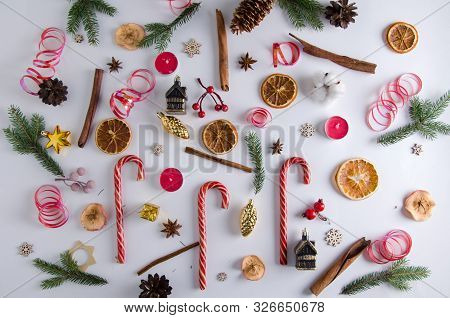 Christmas And New Year Decorations Lie On A White Background: Fir Branches, Lollipops, Candles, Drie