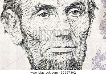 Macro of Abe Lincoln on the US five dollar bill.