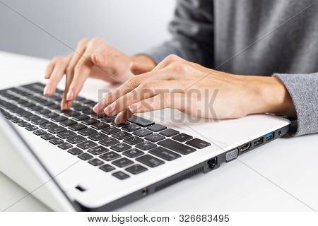 Student Sitting At Desk And Working At Laptop Computer. Close-up Of Female Hand Typing At Notebook C