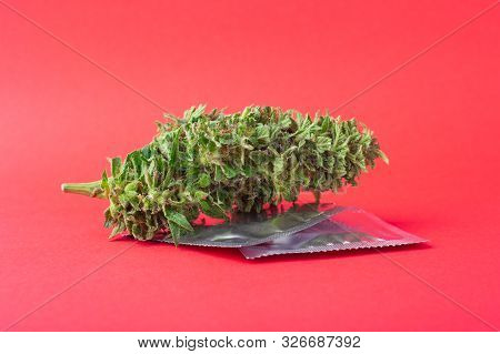 Marijuana And Condoms On Red Background,contraception For Intercourse With Cannabis,natural Aphrodis