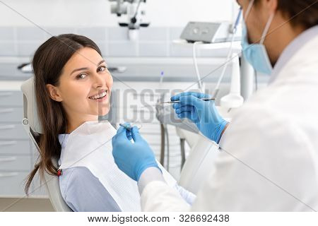 Happy Woman Making Check Up In Modern Dental Office, Doctor Checking Her Teeth, Side View, Empty Spa