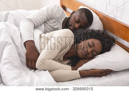 Young African American Couple Napping Together In Bed, Husband Cuddling His Wife From Back.