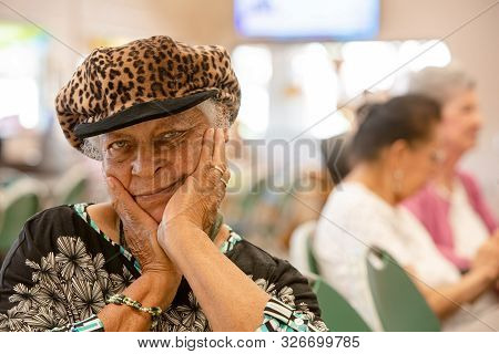 Mature African American Woman In A Busy Senior Center