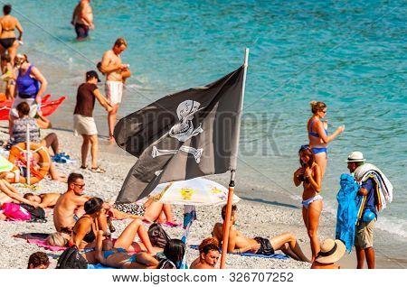 Monterosso Al Mare, Italy - September 02, 2019: Black Jolly Roger Pirate Flag On The Beach Full Of S