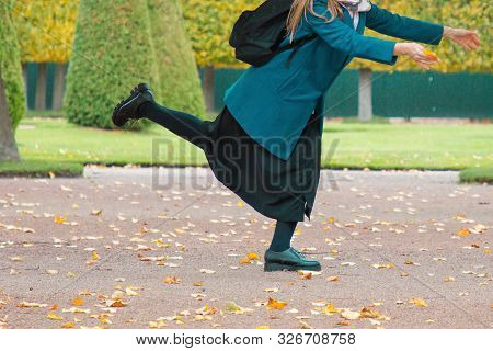 The Concept Of Haste And Tardiness. A Woman Is Fooling Around And Having Fun In The Park, Against Th