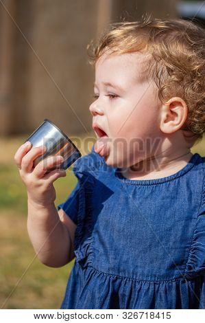 Little Baby Girl 1 Year Old In A Blue Dress, Open Mouth Protruding Tongue, The Child Wants To Drink