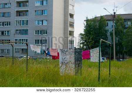 In The Urban Courtyard Among The High-rise Buildings On A Typical Summer Day, Freshly Washed Colored