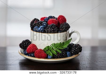 Tea Cup With Berries Closeup On A Wooden Table. Raspberry, Blackberry, Bilberry In A Cup. Beautiful