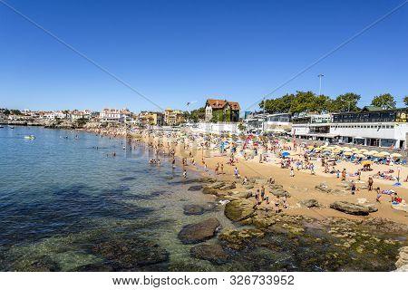 Cascais - August 14, 2019: View Of The Crowded Pretty Little Beach Named Praia Da Duquesa Along The