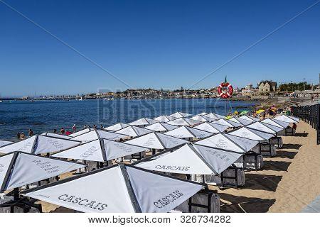 Cascais - August 14, 2019: Rows Of White Umbrellas At The Concessioned Praia Das Moitas Beach, In Ca