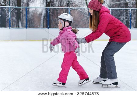 Mom Teaches Her Little Daughter To Skate On The Rink On A Winter Day. Weekends Activities Outdoor In