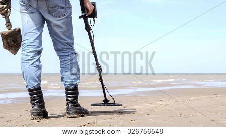 A Man With A Metal Detector And Shovel Exploring A Sea Sandy Beach.