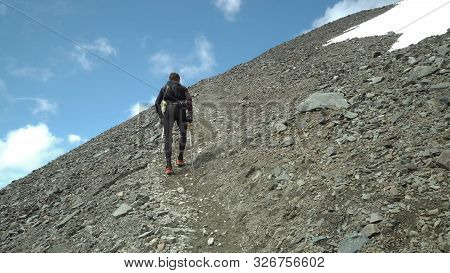 Man Trail Running Into The Mountains With A Backpack And Poles For Hiking.