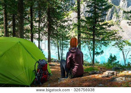 A Girl In A Touring Jacket And A Hat Sitting Green By A Tent With A Backpack And Looking At A Beauti