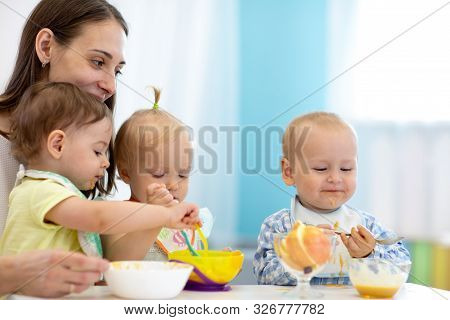Group Of Nursery Babies Eating Healthy Food With Babysitter Help. Lunch Break In Creche. Time To Eat