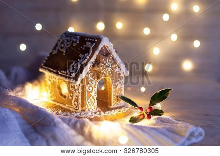 Christmas Gingerbread House At Night, Cozy Decorations On Wooden And Knitted Background With Glares.