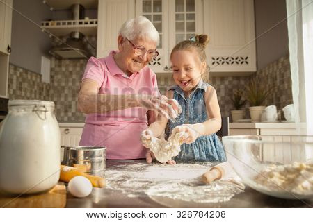 Cute little girl and her grandmother cooking on kitchen.