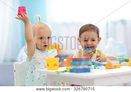 Little Kids Playing In Creche Or Nursery. Developmental Toys For Preschool.