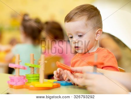 Little Child Boy Playing With Educational Toy In Creche Or Nursery
