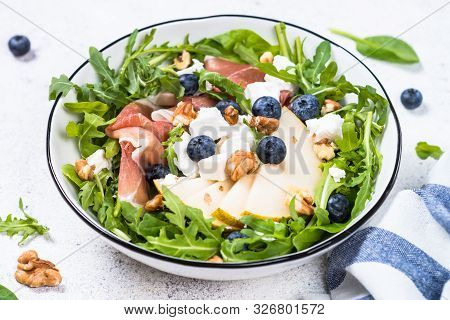 Green Salad With Arugula, Spinach, Pear, Jamon, Blueberries And Feta Cheese On White Background. Hea