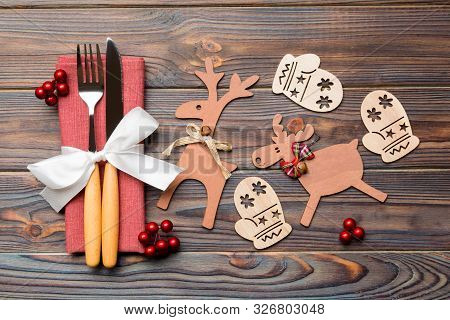 Top View Of Flatware Tied Up With Ribbon On Napkin On Wooden Background. Close Up Of Christmas Decor