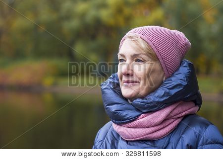 Happy Cheerful Elderly Senior Mature Woman In Winter Hat And Scarf Walking In A Golden Autumn Park W