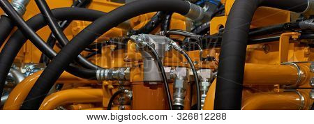 Banner With Close Up View Of Hydraulic Pipes Of Heavy Industry Machine. Low Key.
