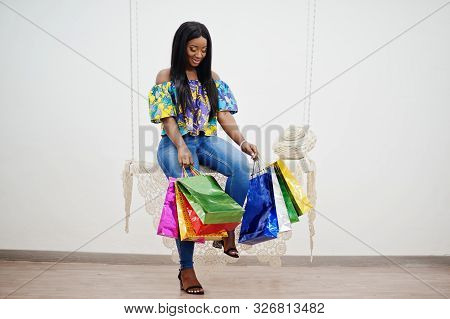 Black African American Millennial Girl In Living Room Hold Colored Shopping Bags, Happy Dark Skinned