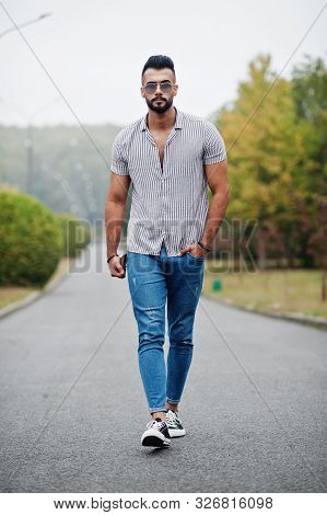 Fashionable Tall Arab Beard Man Wear On Shirt, Jeans And Sunglasses Posed On Park And Hold Wallet At