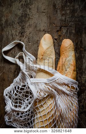 Fresh Rosy Baguettes In A String Bag On A Dark Wooden Retro Background. Top View, Copy Space