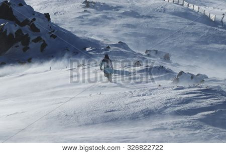 Snowboarding Snowboard Snowboarder. Freerider In Colored Clothes Walks With His Board Through Windst