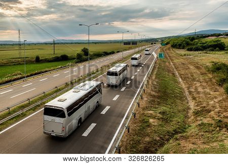 Caravan Or Convoy Of Four Buses In Line Traveling On A Highway Country Highway