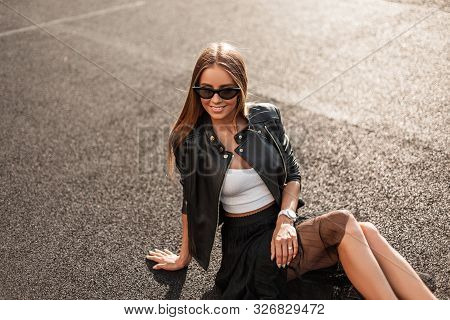 Cheerful Young Hipster Woman In A Stylish Leather Jacket In Trendy Sunglasses In An Elegant Black Sk