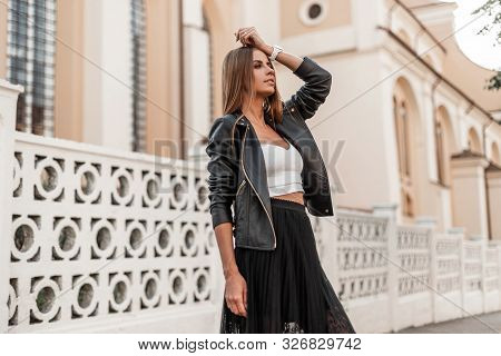 Trendy European Young Girl In An Fashionable Autumn Black Leather Jacket In An Black Elegant Long Sk