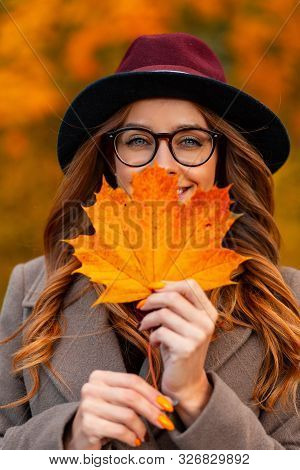 Portrait Of A Positive Beautiful Young Woman In Stylish Glasses In An Elegant Burgundy Hat In An Aut