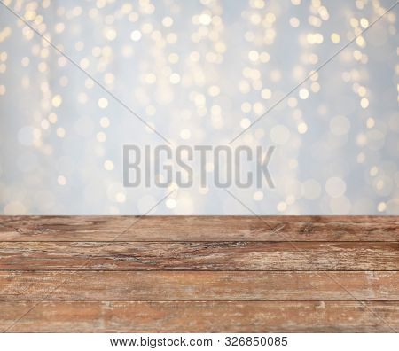 holidays concept - empty wooden surface or table with christmas golden lights background