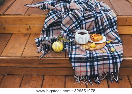 Autumn Picnic With Hot Tea And Cinnabon On A Cozy Wooden Porch. Fall Atmosphere. Slow Living Concept